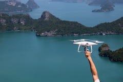 UAV of Hommel de camera vliegt omhoog van de handen in de blauwe hemel met Stock Foto