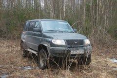 UAZ爱国者在泥黏附了,在森林, 4月 免版税库存图片