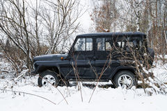 UAZ猎人,传奇军用俄国汽车在冬天森林里停放了 库存图片