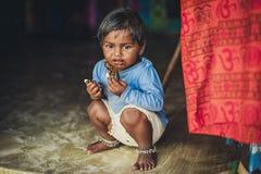 Ubóstwo, obrazek biedna Indiańska dziewczyna w starym obdartym odzieżowym obsiadaniu na podłodze troszkę Czekoladowy dziecko fotografia stock