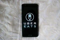 Uber吃在一个黑电话的app有白色纹理背景 图库摄影