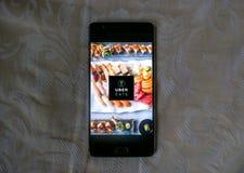 Uber吃在一个黑电话的app有白色纹理背景 免版税库存图片