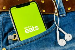 Uber吃在苹果计算机iPhone x智能手机屏幕特写镜头的应用象在牛仔裤口袋 Uber吃app象 3d网络照片回报了社交 Socia 免版税库存图片