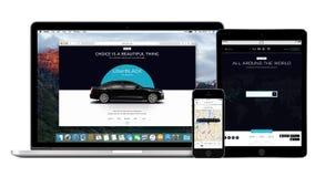 Uber app en el iPhone de Apple, Macbook favorable y exhibiciones del iPad Fotos de archivo