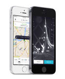 Uber app startup page and Uber search cars map on white and black Apple iPhones Royalty Free Stock Photos