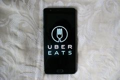 Uber Eats app on a black phone with white texture background stock photography