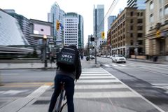 Uber Eats delivery man on a bicycle waiting to cross a street in the center of Toronto, Ontario, with a motion blur effect. Picture of a food courrier from Uber royalty free stock image