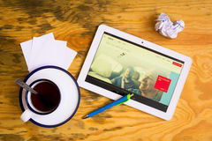 Uber. Flat lay of tablet, cup of tea, pen and papers. Uber is on the screen stock photo