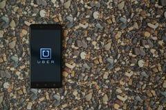 Uber-Logo auf Smartphone auf Hintergrund von kleinen Steinen Stockfoto