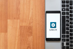 Uber on smartphone screen. Los Angeles, USA, july 18, 2017: Uber on smartphone screen placed on the laptop on wooden background Stock Photography
