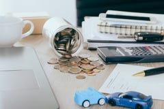 Ubezpieczenia samochodu pojęcie: Samochodowa żądanie forma z samochód zabawki trzaskiem na biurku z pieniądze przepływem z słoju  Obraz Royalty Free