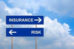 Ubezpieczenie i ryzyko na błękitnym drogowym znaku Zdjęcia Stock