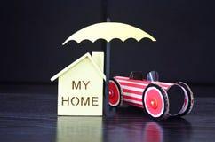Ubezpieczenie, parasol ochrania dom i samochód Obraz Stock