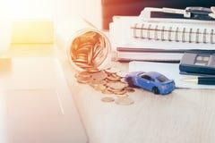 Ubezpieczenie samochodu i loanconcept: Samochód zabawka na biurku z pieniądze przepływem z słoju menniczego banka, ciepły brzmien Obrazy Royalty Free