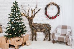 Ubicación del ` s del Año Nuevo en el estudio con un ciervo, adornado con un árbol de navidad, regalos, una cesta de conos Foto de archivo libre de regalías