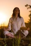 Ubicazione bella della donna di yoga contro l'alba Fotografie Stock