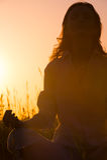 Ubicazione bella della donna di yoga contro l'alba Fotografia Stock Libera da Diritti