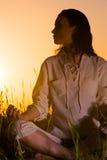 Ubicazione bella della donna di yoga contro l'alba Immagini Stock Libere da Diritti
