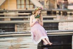 Ubicazione della ragazza sul pilastro sul lago Immagini Stock