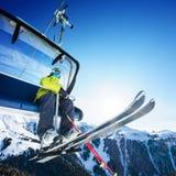 Ubicazione dello sciatore sullo ski-lift - sollevi al giorno soleggiato ed alle montagne Fotografia Stock