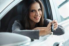Ubicazione di Holding Car Keys dell'autista della donna in sua automobile nuova Immagini Stock