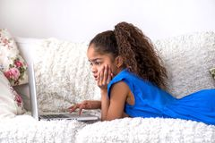 Ubicazione nera dell'adolescente su uno strato con un computer portatile Fotografie Stock