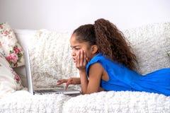 Ubicazione nera dell'adolescente su uno strato con un computer portatile Fotografia Stock