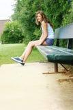 Ubicazione teenager su un banco Immagine Stock