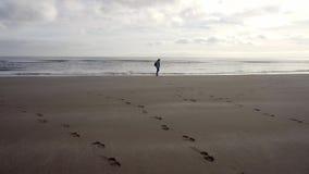 Ubierająca kobiety pozycja na plażowym seashore, rusza się wzdłuż linii brzegowej zdjęcie wideo