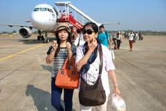 UBONRATCHATHANI TAILANDIA 8 DE MARZO DE 2013: Turistas que bajan de un avión de aire de Air Asia en el aeropuerto de Ubonratchath Imágenes de archivo libres de regalías
