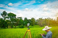 UBONRATCHATHANI, THAILAND-SEPTEMBER 26, 2017 : Asian smart engineer or surveyor is working on controller screen for surveying land. In rice field. GPS surveying stock photo