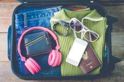 Ubraniowy podróżnika ` s paszport, portfel, szkła, zegarki, mądrze telefonów przyrząda na drewnianej podłoga w bagażu przygotowyw Fotografia Stock