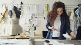 Ubraniowy projektanta enterpreneur jest mknącym mieszkaniem nieatutowym szaty kawa na pracownianym biurku z mądrze telefonem i na zdjęcie wideo