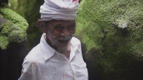 UBUD,印度尼西亚- 2017年2月2日:未知的笑和审阅狂放的森林和密林的巴厘语老人 股票视频