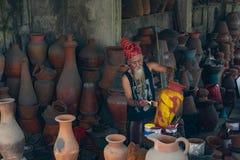 UBUD, BALI 27 AVRIL 2019 un vieil artisan blanc-barbu de poterie portant une cravatte principale ethnique colore sa poterie en sa images stock