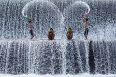 Poverty boys having fun at Tukat Unda dam, Bali royalty free stock image