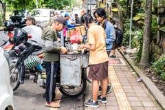 Ubud, Bali Indonezja, Styczeń, - 2019: Dziewczyny w mundurka szkolnego kupienia jedzeniu od sprzedawcy ulicznego podczas przerwy  zdjęcie stock