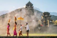 Ubud, Bali - 30 luglio 2016 Mostra il maschio tradizionale di balinese e delle offerti religiose cerimoniali femminili e dell'abb immagini stock libere da diritti