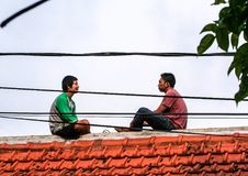 Two young man sitting on the roof. Cityscape of Ubud. stock photos