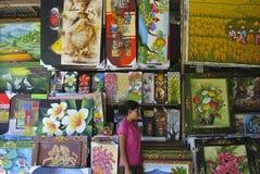 UBUD, INDONÉSIA, em maio de 2016, mulher em pinturas compram no mercado de Ubud o Ubud Art Market, referido localmente como o ` d fotografia de stock royalty free