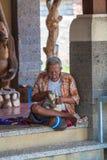 UBUD, INDONESIË - AUGUSTUS 29, 2008: Inheemse mens die houten sta snijden Stock Foto's