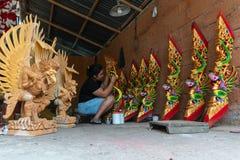 UBUD/INDONESIA- 27-ОЕ АПРЕЛЯ 2019: Женский мастер от Ubud делает дракона высекая и крася его используя яркое и привлекательное стоковое изображение rf