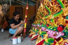 UBUD/INDONESIA- 27 DE ABRIL DE 2019: Um artes?o f?mea de Ubud est? fazendo o drag?o que cinzela e que colore o usar-se brilhante  fotos de stock