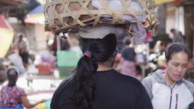 UBUD-STAD, BALI, INDONESIEN - FEBRUARI 2, 2017: Den fattiga indonesiska kvinnan på morgonmarknaden bär en stor korg på henne lager videofilmer