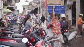UBUD-STAD, BALI, INDONESIEN - FEBRUARI 2, 2017: Fattigt indonesiskt folk som säljer och köper sund mat på morgonen lager videofilmer