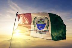 Ucayali Region of Peru flag textile cloth fabric waving on the top sunrise mist fog. Beautiful stock photos