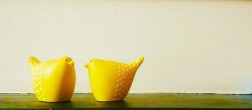 Uccelli ceramici gialli contro fondo bianco Immagini Stock