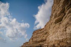 Uccelli che sorvolano montagna Cielo nuvoloso e roccia blu fotografia stock libera da diritti