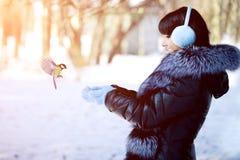 Uccelli d'alimentazione di inverno della giovane donna donna di inverno su fondo di w Fotografia Stock