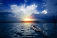 Uccelli di sogno di mattina della barca che volano sul cielo drammatico al sunse di alba Immagine Stock Libera da Diritti